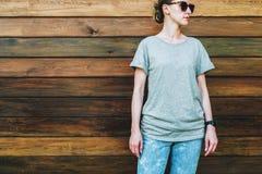 Bekläda beskådar Är den iklädda gråa t-skjortan för den unga millennial kvinnan ställningar mot den mörka wood väggen Arkivfoton