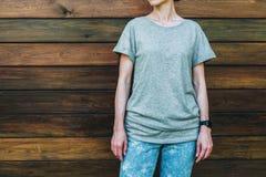 Bekläda beskådar Är den iklädda gråa t-skjortan för den unga millennial kvinnan ställningar mot den mörka wood väggen Arkivbild