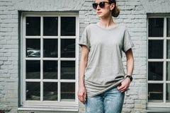 Bekläda beskådar Är den iklädda gråa t-skjortan för den unga millennial kvinnan ställningar mot den gråa tegelstenväggen Arkivbild