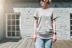 Bekläda beskådar Är den iklädda gråa t-skjortan för den unga millennial kvinnan ställningar mot den gråa tegelstenväggen Arkivfoton