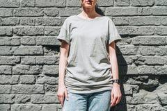 Bekläda beskådar Är den iklädda gråa t-skjortan för den unga millennial kvinnan ställningar mot den gråa tegelstenväggen Royaltyfria Foton