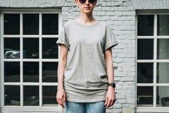 Bekläda beskådar Är den iklädda gråa t-skjortan för den unga millennial kvinnan ställningar mot den gråa tegelstenväggen Royaltyfria Bilder