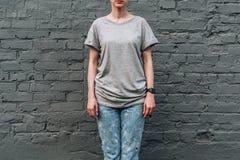Bekläda beskådar Är den iklädda gråa t-skjortan för den unga millennial kvinnan ställningar mot den gråa tegelstenväggen Royaltyfri Bild
