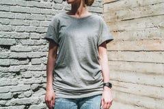 Bekläda beskådar Är den iklädda gråa t-skjortan för den unga millennial kvinnan ställningar mot den gråa tegelstenväggen Arkivbilder