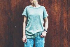 Bekläda beskådar Är den iklädda gråa t-skjortan för den unga millennial kvinnan ställningar mot väggen av rostig metall Royaltyfria Bilder
