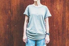 Bekläda beskådar Är den iklädda gråa t-skjortan för den unga millennial kvinnan ställningar mot väggen av rostig metall Royaltyfri Fotografi