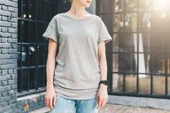 Bekläda beskådar Är den iklädda gråa t-skjortan för den unga millennial kvinnan ställningar mot den gråa wood väggen Arkivbilder