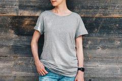 Bekläda beskådar Är den iklädda gråa t-skjortan för den unga millennial kvinnan ställningar mot den gråa wood väggen Royaltyfria Bilder