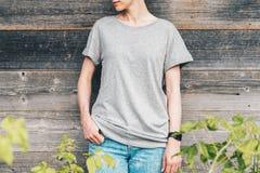 Bekläda beskådar Är den iklädda gråa t-skjortan för den unga millennial kvinnan ställningar mot den gråa wood väggen Royaltyfria Foton