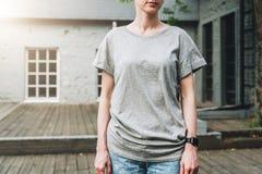 Bekläda beskådar Är den iklädda gråa t-skjortan för den unga millennial kvinnan ställningar på stadsgatan Åtlöje upp Royaltyfria Bilder