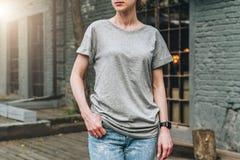 Bekläda beskådar Är den iklädda gråa t-skjortan för den unga millennial kvinnan ställningar på stadsgatan Åtlöje upp Royaltyfri Bild
