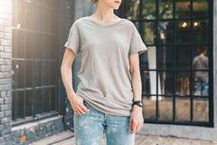 Bekläda beskådar Är den iklädda gråa t-skjortan för den unga millennial kvinnan ställningar på stadsgatan Åtlöje upp Royaltyfri Fotografi