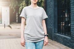Bekläda beskådar Är den iklädda gråa t-skjortan för den unga millennial kvinnan ställningar på stadsgatan Åtlöje upp Arkivbild