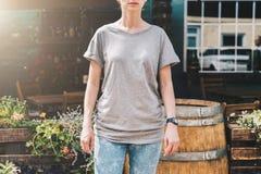 Bekläda beskådar Är den iklädda gråa t-skjortan för den unga millennial kvinnan ställningar på stadsgatan Åtlöje upp Royaltyfria Foton