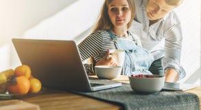 Bekläda beskådar Morgon breakfastYounggift par i kök Gravida kvinnan sitter på tabellen och använder bärbara datorn Arkivbilder