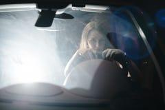 Bekläda beskådar Stående av den härliga kvinnan som kör hennes lyxiga bil på natten Trafikljusen bakom arkivfoton