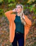 Bekläda för varje dag Förtjusande blondin för flicka som poserar i defocused varm och hemtrevlig bakgrund för dräkthöstnatur cozy fotografering för bildbyråer