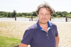 beklär bärande blått för mannen att posera i den medeltida Europa för havslandskap byn arkivbild