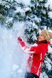 Beklär den bärande vintern för flickan skakar av från filialer av träd Royaltyfria Foton