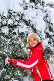 Beklär den bärande vintern för flickan skakar av från filialer av träd Arkivfoto