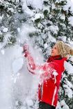 Beklär den bärande vintern för flickan skakar av från filialer av träd Arkivbild