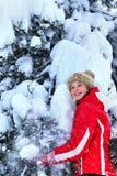 Beklär den bärande vintern för flickan skakar av från filialer av träd Fotografering för Bildbyråer