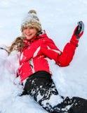 Beklär den bärande vintern för tonåringflickan att ligga i djup snö Arkivbild