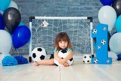 Beklär iklädda sportar för litet gladlynt barn sammanträde på golvet nära ett fotbollmål som ser en stor fotbollboll Första fotografering för bildbyråer