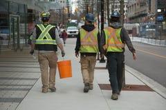 Beklemmingsarbeiders die moderne straat lopen stock fotografie