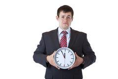 Beklemtoond, drepressed zakenman houdt klok royalty-vrije stock foto