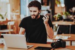 Beklemtoond Guy Holds Phone Works op Laptop binnen royalty-vrije stock foto
