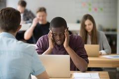 Beklemtoonde Afrikaans-Amerikaanse ondernemer die slechte hoofdpijn hebben bij wo royalty-vrije stock afbeelding