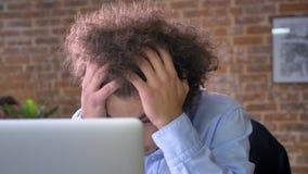 Beklemtoonde arbeider met krullend haar en snor die zijn hoofd, problemen met zaken, moderne bureauachtergrond houden stock video