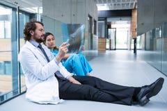 Beklemtoonde arts en verpleegster zitting die op vloer Röntgenstraalrapport onderzoeken royalty-vrije stock afbeelding