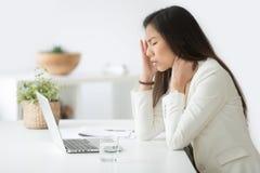 Beklemtoonde Aziatische onderneemster die hoofdpijn of migraine hebben op het werk stock fotografie