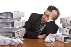 Beklemtoonde bedrijfsmensenzitting die in bureau wordt gefrustreerd stock afbeelding