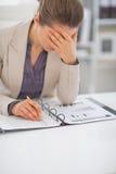 Beklemtoonde bedrijfsvrouw met documenten op het werk Stock Foto's