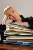 Beklemtoonde bureaustafmedewerker met stapel van administratie Stock Foto