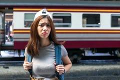 Beklemtoonde gedeprimeerde jonge Aziatische dametoerist die schok voelen die en na juffrouw een trein frustreert Probleem en reis royalty-vrije stock afbeelding