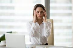 Beklemtoonde gefrustreerde vrouwelijke werknemer die hoofdpijn of migraine voelen royalty-vrije stock fotografie