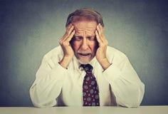 Beklemtoonde hopeloze bejaarde bedrijfsmens in depressiezitting bij de bureaulijst Royalty-vrije Stock Fotografie