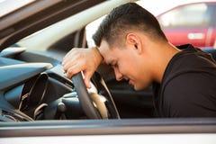 Beklemtoonde jonge mens in een auto Stock Foto
