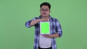 Beklemtoonde jonge te zware Aziatische hipstermens die digitale tablet tonen stock video