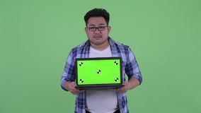 Beklemtoonde jonge te zware Aziatische hipstermens die laptop tonen stock video