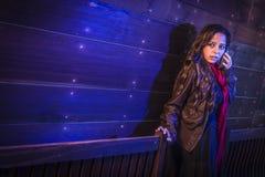 Beklemtoonde Jonge Vrouw in Donkere Gang die Celtelefoon met behulp van Stock Foto