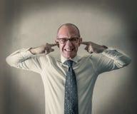 Beklemtoonde manager met zijn vingers in zijn oren royalty-vrije stock afbeelding