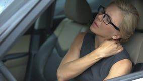 Beklemtoonde onderneemster die hals aan ongemak lijden, die in auto, het sedentaire leven zitten stock videobeelden