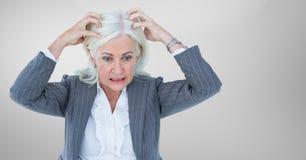 Beklemtoonde oudere vrouw tegen grijze achtergrond stock afbeelding