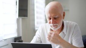 Beklemtoonde overwerkte vermoeide hogere mens in het witte werken aan laptop thuis Het wrijven van zijn pijnlijke ogen stock footage