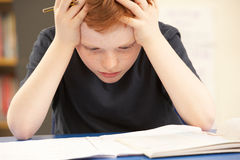 Beklemtoonde Schooljongen die in Klaslokaal bestudeert Royalty-vrije Stock Afbeelding